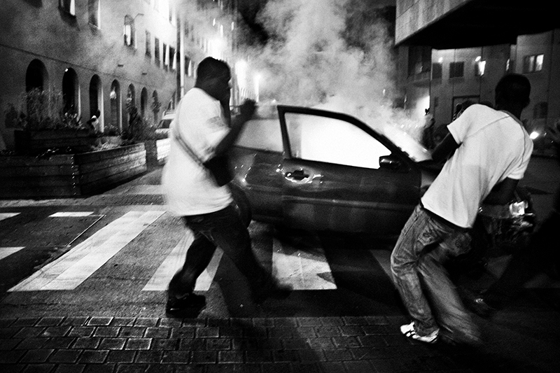 A stolen car is burnt in Saint Denis on the night of July 14, Bastille Day, the French National Day. More than 10,000 cars were subsequently burnt over three days during the 2005 riots and on New Year's Eve 2012, 1,200 cars were burnt. Paris, France, July 2007.