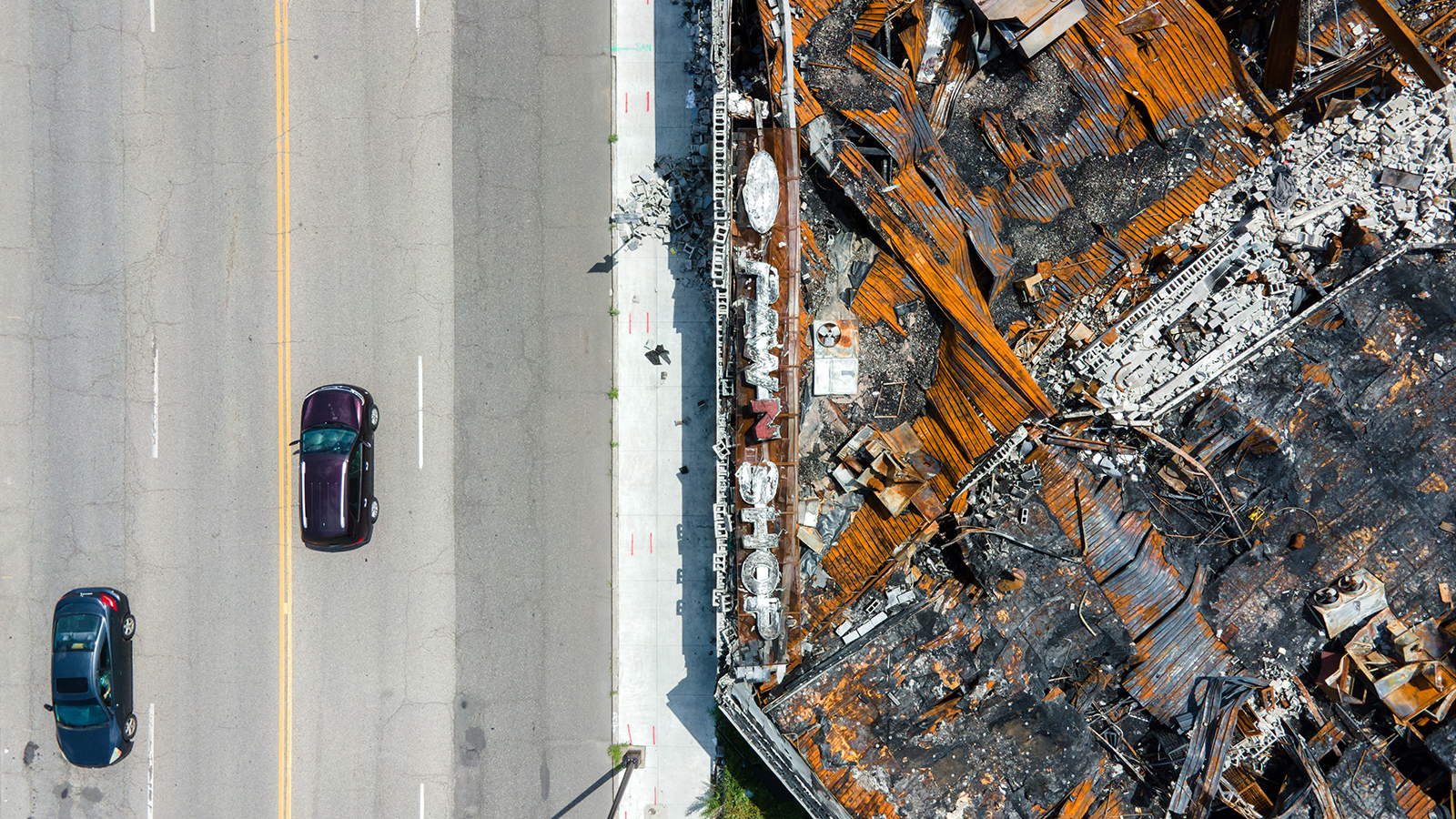 MINNEAPOLIS—Vehicles drive by a pawn shop, which was gutted, during the unrest following the murder of George Floyd.